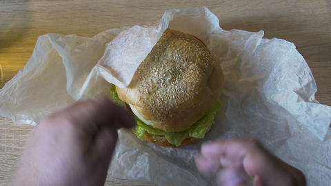 Male unwrapping hamburger on home table, preparation for lunch, unhealthy eating Live Action