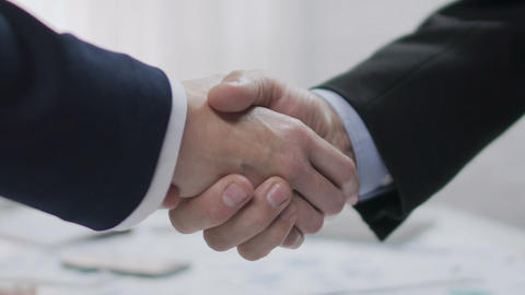 Two male business partners shaking hands, profitable agreement, co-operation Live Action