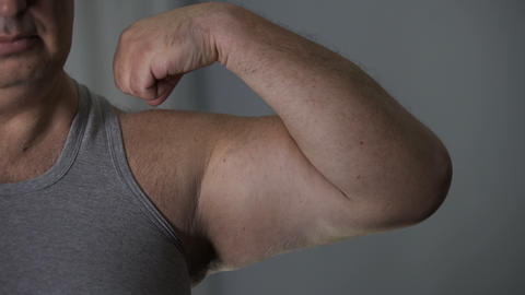Close-up of unhealthy overweight male showing his weak biceps before camera Live Action