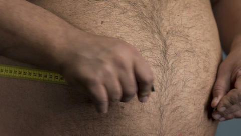 Overweight man trying to measure his belly at home close up, weight loss diet Live Action