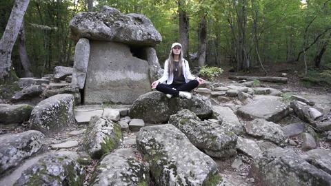Girl sitting and meditating near ancient dolmen Footage