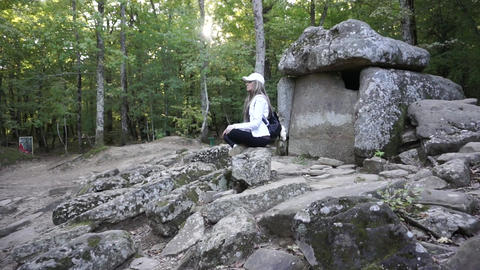 Girl meditating near stone dolmen in mountain forest GIF