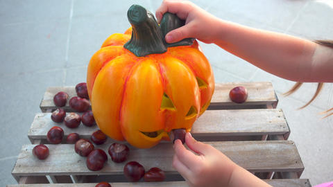 Little girl playing feeding chestnuts to halloween pumpkin Live Action