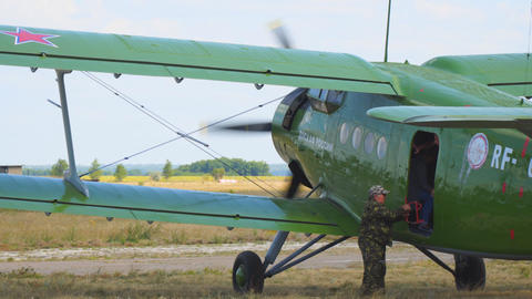 Old biplane aircraft at the airfield. Passengers leave the plane Live Action