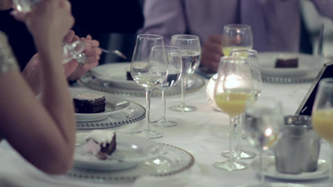 Men and women sit at a table and eat cake slices and drink mineral water 82 Footage