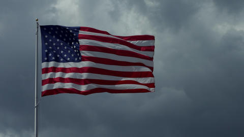American Flag Waving With Dark Sky And Clouds In Background Footage