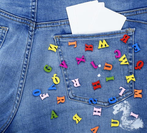 colored wooden letters scattered on blue jeans Photo
