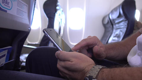 Business Man Travelling in Aircraft Using Mobile Phone during Flight Live Action