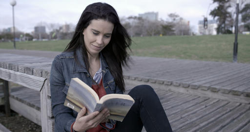 Woman reading and looking at the camera outdoors – 4K Footage