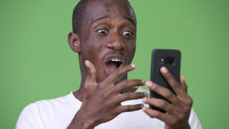 Young happy African man looking shocked while using phone Footage