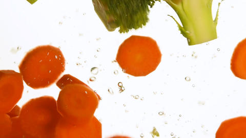 Close up broccoli and carrot thrown float in water Footage