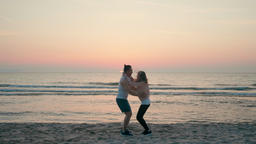 Loving Happy Couple is and Laughing Whirling on Sea Beach at Sunset in Summer ビデオ