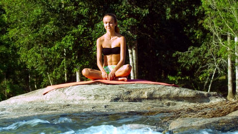 young woman relaxes in position Half Lotus by foamy river Footage