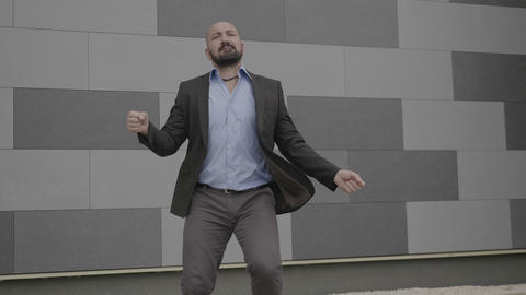 Confident young businessman celebrating success or achievement dancing and Footage