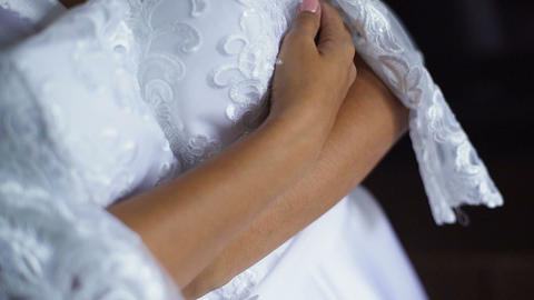 Beautiful bride in white wedding negligee holding and hugging wedding dress Footage
