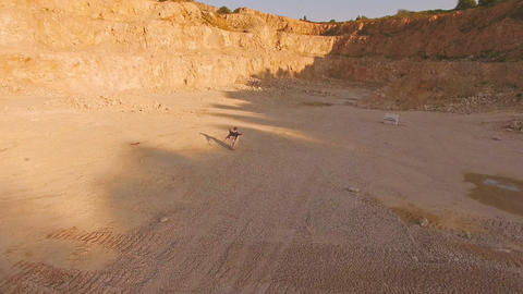A young woman walks along the yellow sand among the yellow mountains barefoot to Footage