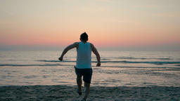 Happy Man is Running Fast and Jumping High at the Sea Coast on Beach at Sunset ビデオ