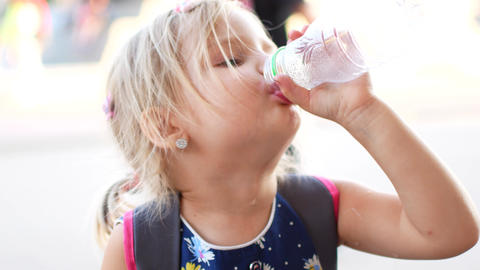 The child blond girl with pleasure drink water outdoors. A child is drinking Footage