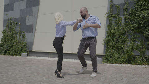Young skillful business couple dancing latino frestyle outdoor near a business Footage
