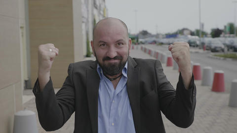 Adult business man entrepreneur expressing the joy of winning pumping fists Footage