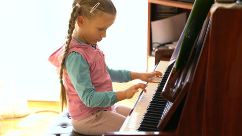 little girl learns to play the piano 영상물