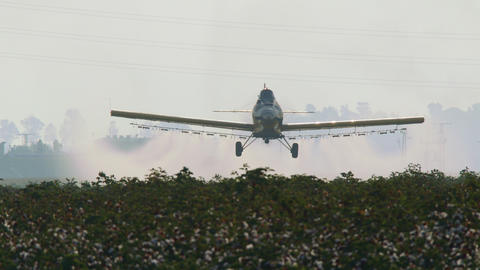 Crop duster spraying chemicals over a cotton field - slow motion ビデオ