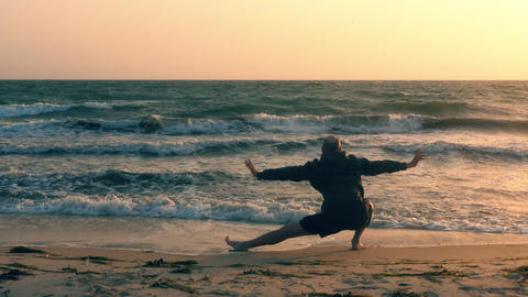Sportive man stretching and practicing yoga on seashore at sunrise Live Action