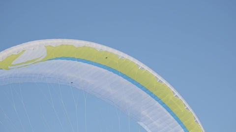 Winter sports . Bright yellow parachute against a blue sky ビデオ