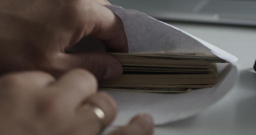 Man looks into the envelope which is pack of 100 dollar bills Archivo