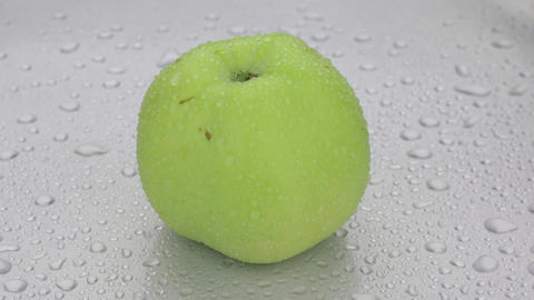 Rotation of a whole ripe apple in drops of dew lying on a white wet background Live Action