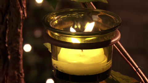 A lit candle slowly burns in a green bowl in the temple Footage