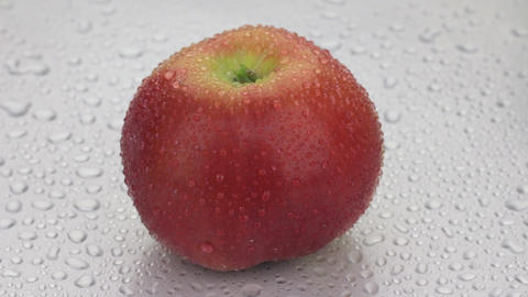 Rotation of a whole ripe apple in drops of dew lying on a white wet background ビデオ