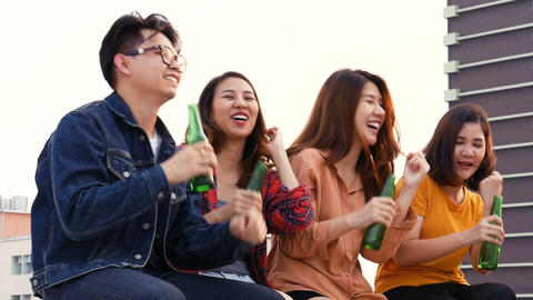 Group of Asian young people clinking bottles of beer party on rooftop ビデオ
