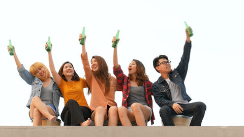 Group of asian young people clinking bottles of beer party on rooftop Live Action