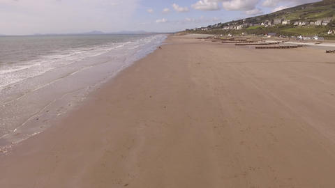 Aerial footage flying backwards over Barmouth beach Live Action