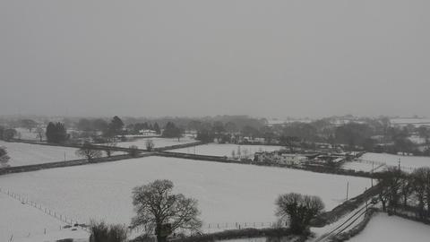 Ascending aerial footage snowing rural area uk Footage