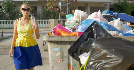 Woman throwing plastic bottle into street garbage Footage