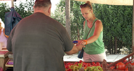 Woman paying for vegetables on the market Footage