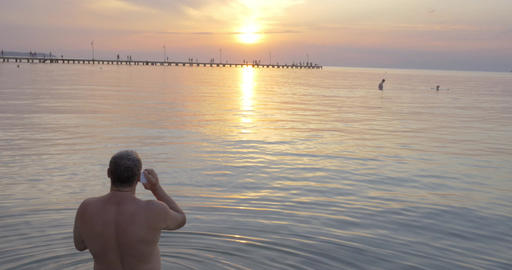 Back view of man talking over phone while watching sunset Footage