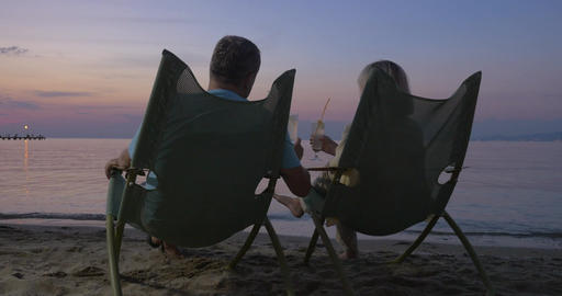 Mature couple relaxing on the beach and drinking cocktails Footage