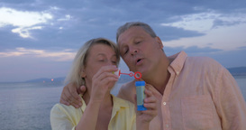 Mature couple blowing bubbles on the coast Footage
