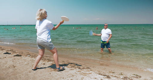 Mature Couple Playing Racket Ball on the Beach Footage
