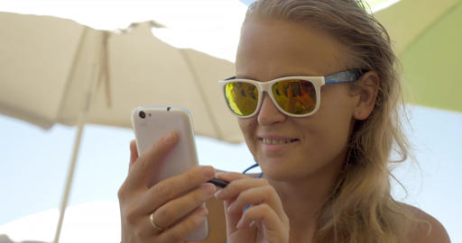 Woman in sunglasses using cell on beach Footage