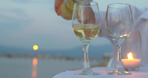 Pouring wine in glasses at seaside Footage