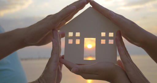 Hands Holding House Silhouette against Sun Footage