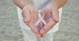 Breast cancer awareness ribbon in womans hands Footage