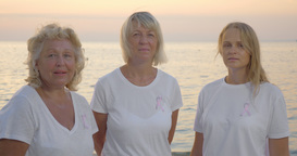 Three women with pink breast cancer awareness ribbons Footage