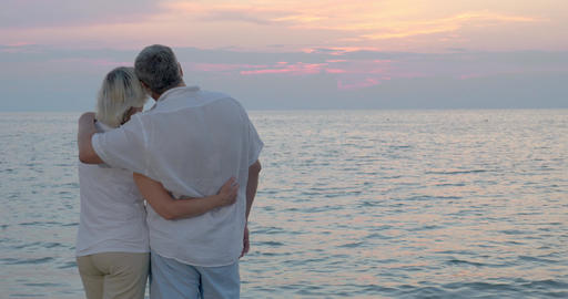 Loving senior couple enjoying evening seascape Footage