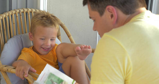 Smiling Boy Listening His Father Reading a Book Footage