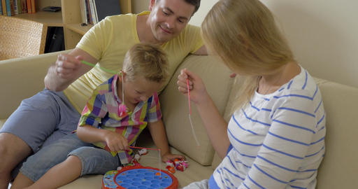 Parents and child playing fishing game at home Footage